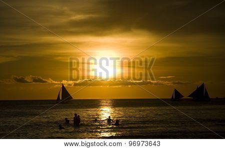 Sunset and sailing boats on white beach in Boracay Philippines