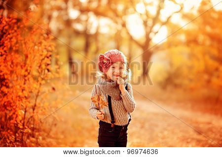 cute happy child girl playing with stick and leaves on the walk in autumn forest