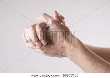 A man washes his hands with soap and water