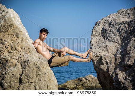 Young Man Spanning Gap Between Coastal Boulders