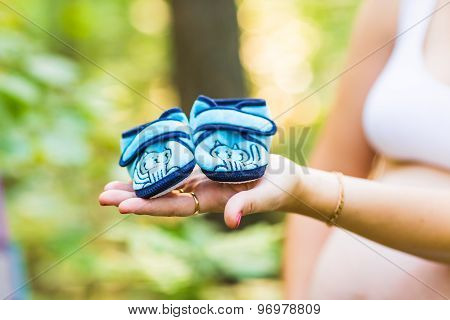 pregnant woman with a baby's bootees