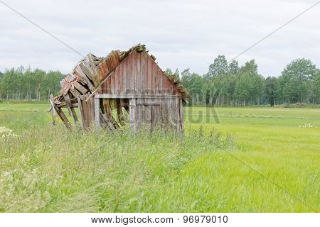 Tumbledown Barn On A Field
