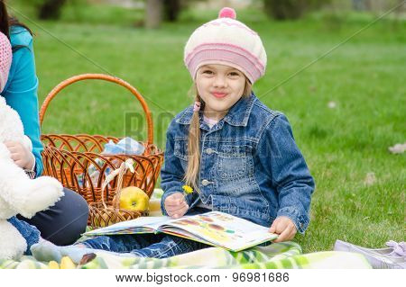 Girl Of Five Years Sitting On A Green Lawn