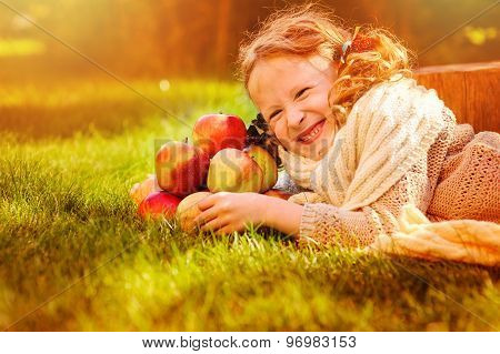 happy child girl playing with red apples in sunny autumn garden