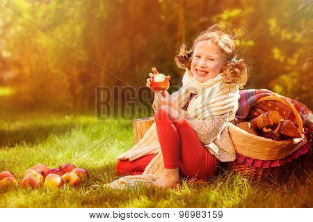 happy child girl eating fresh red apples in sunny autumn garden