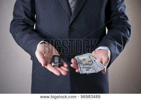 Car Key And Hundred-dollar Bills In The Hands Of A Businessman