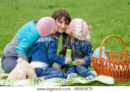 Two Daughters Kissing Mother While On A Picnic