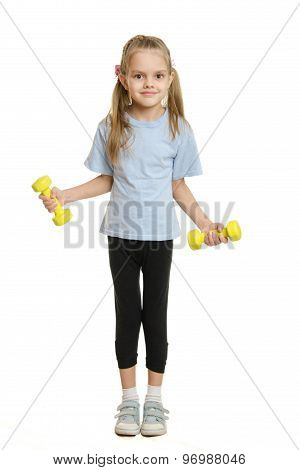 Six Year Old Girl Athlete Engaged In Exercise With Dumbbells