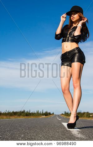 Woman In A Black Leather Clothes Staying On The Road