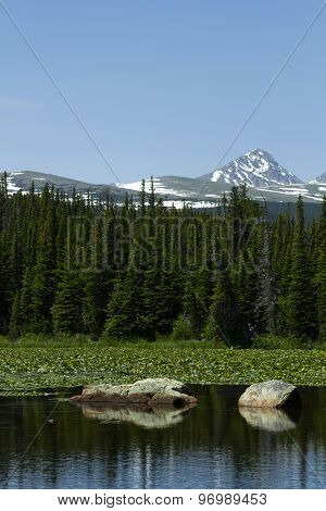 Dramatic Red Rock Lake With Huge Stones, Forest, And Mountains