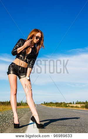 Sexy Woman In A Black Leather Clothes On The Road