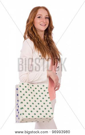 Cute smiling girl in light short coat with plastic bags isolated on white