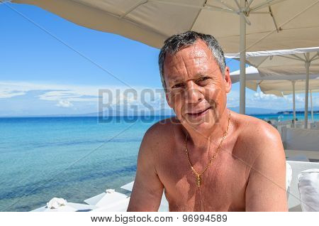 Senior Retired Man With Salt And Pepper Hair On Vacation In A Beach Bar With White Umbrellas At The