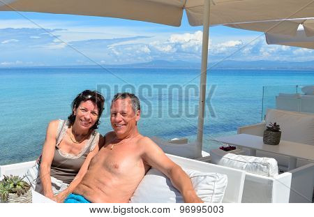 Loving Couple On Holiday At A Beach Bar By The Transparent Turquoise Mediterranean Sea