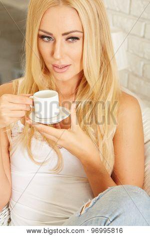 Beautiful elegant woman barefoot drinking coffee