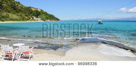 Beautiful Cove By The Crystalline Turquoise Mediterranean Sea In Greece With Fishing Boat And Hills