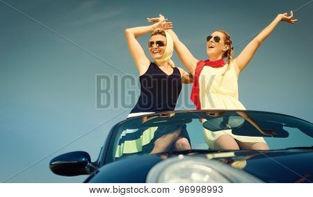 Two women in convertible car enjoying car trip stretching their arms