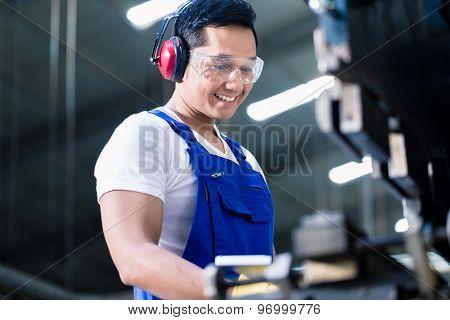 Asian worker operating metal skip in factory