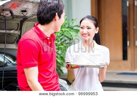 Asian couple having coffee break at new car on driveway to their home