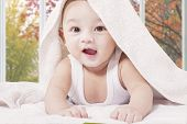 stock photo of crawl  - Closeup of excited male infant crawling on the bed under a towel while smiling at the camera - JPG