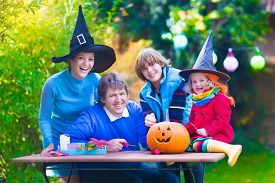 image of jack o lanterns  - Family carving pumpkin at Halloween. Dressed up child trick or treating. Kids and parents trick or treat. Child in witch costume playing in autumn park. Toddler kid with jack-o-lantern. ** Note: Soft Focus at 100%, best at smaller sizes - JPG