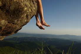 image of barefoot  - Beautiful landscape view from high mountaing on green hills with wood and human female legs barefoot of girl sitting on rock on natural blue sky copyspace background horizontal picturepicture - JPG