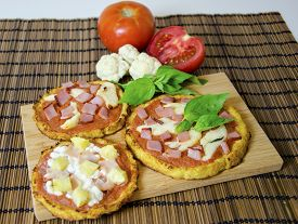 image of crust  - Three small round baked pizzas made of cauliflower crust and topped with bacon ham halloumi cheese cottage cheese lountza pineapple turkey tomato sauce and basil on a wooden chopping board and bamboo tablecloth - JPG