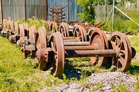 stock photo of train-wheel  - A stockpile of old rusty and abandoned train wheels lying in the grass close to train service depot - JPG