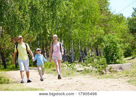 Retrato de três membros da família andando estrada no verão