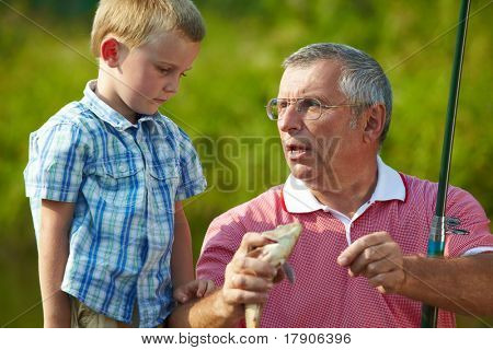 Photo of grandfather telling his grandson about the fish caught by them