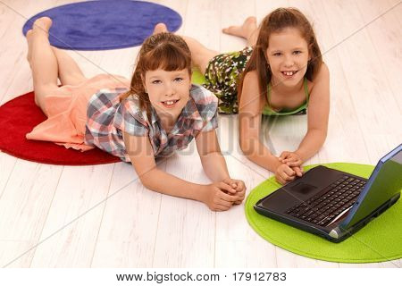 Portrait of smiling small girls lying on floor using laptop computer at home, looking at camera.?