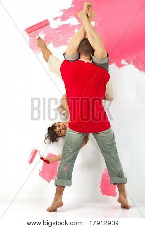 Cheerful young couple of workers painting a wall with roller arsy-versy