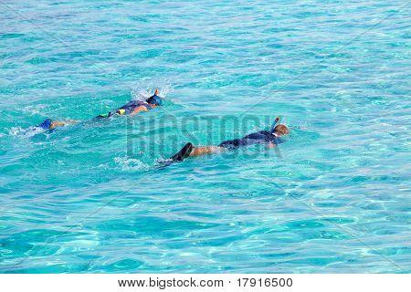 zwei Männer mit Masken und Rohre Schwimmen synchron am Ozean