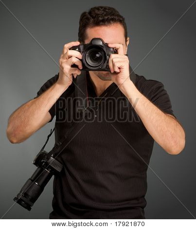 Man in black shooting with his camera with an extra one hanging from the strap