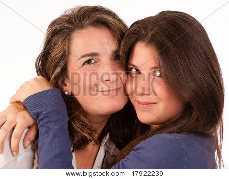 Close-up portrait of a mother and her teenage daughter cuddling