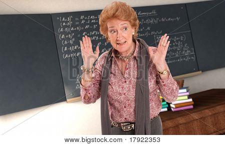Maths teacher with an impatient gesture in and empty classroom