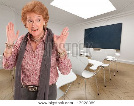 teacher with an impatient gesture in and empty classroom
