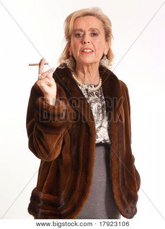 Portrait of an elegant senior lady in a mink coat smoking a cigar