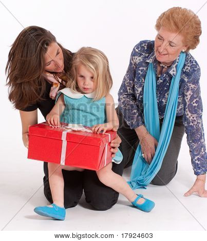 A mother and grandmother watching a little girl open a gift box
