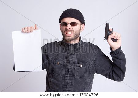 Dangerous looking man holding a gun and a blank paper sheet