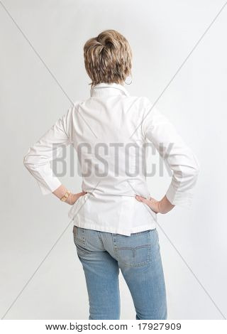 Rear view of a woman looking at something with hands on her hips
