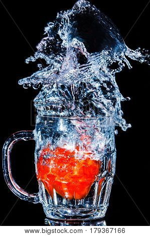 Artistic splash of a tomato created after being dropped into a clear goblet.