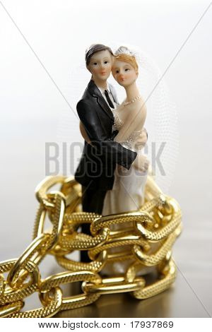 Metaphor of marriage as a loss of freedom. Wedding figurines and golden chain