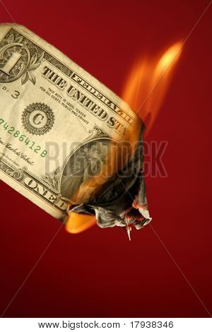 Dollar note, american currency burning in fire over red background, studio shot
