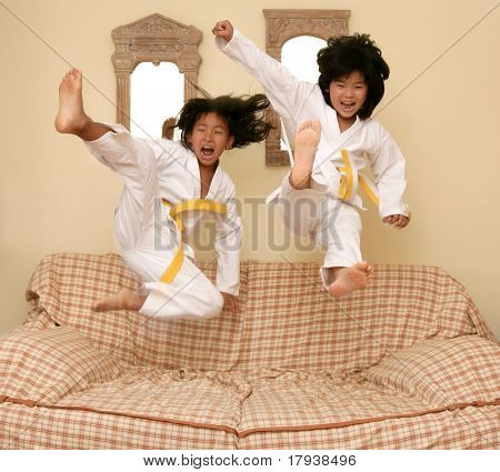 Two little asian judo dressed girls jumping over the sofa at home