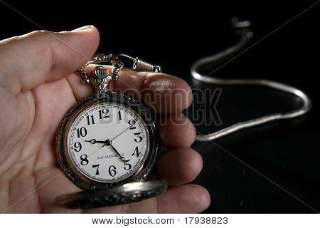 Antique vintage pocket watch on human hand over black