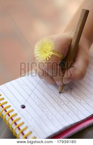 Children hand with funny finger yellow ring writing on a notebook