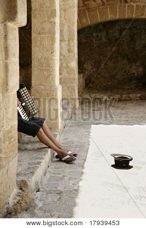 Beggar hidden accordion musician with hat on floor on Ibiza castle