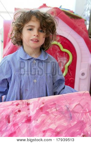 Beautiful preschooler student little girl showing her pink artwork