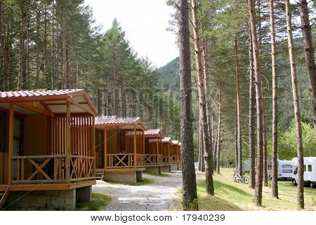 Forest wooden cabins in a mountain pine camping Pyrenees